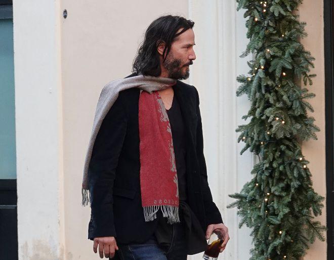 Keanu con bufanda y una copa de vino