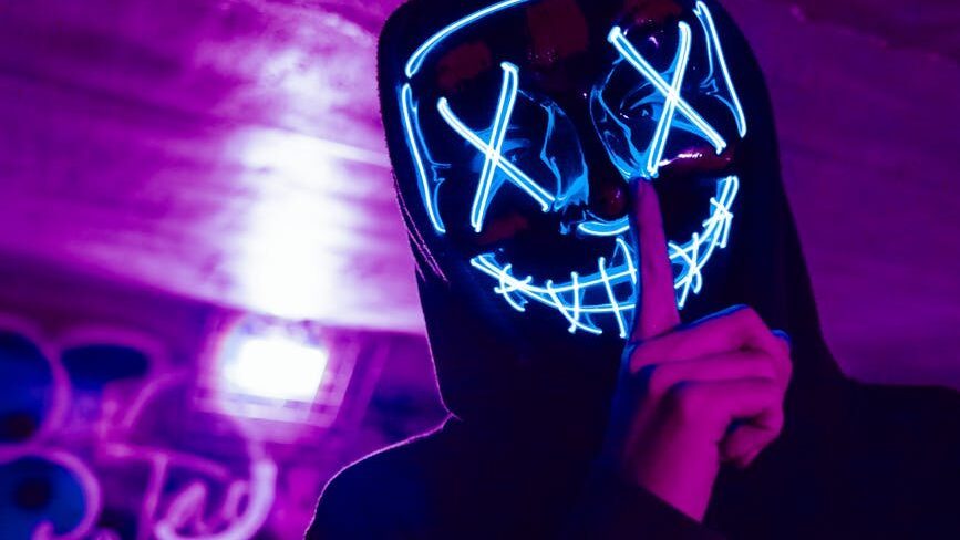 person wearing led mask doing silence gesture