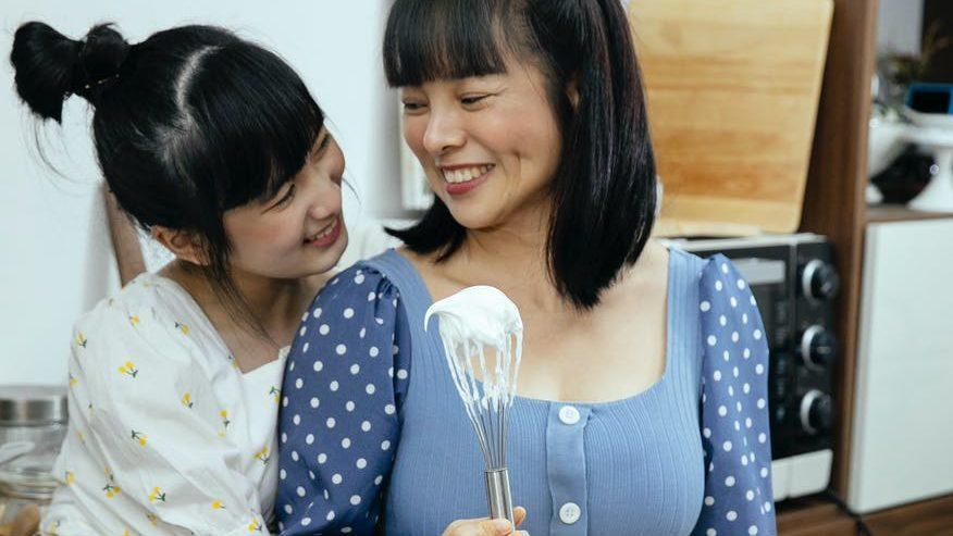 smiling asian mother with daughter preparing meringue cookies at home